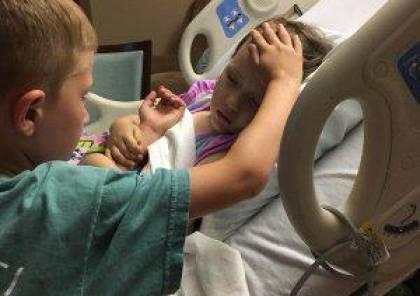 صورة مؤثّرة.. صبي يُودّع شقيقته الصغرى على فراش الموت